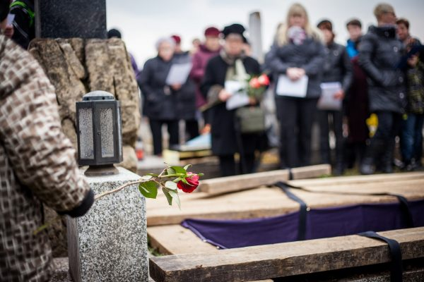 Group of mourners staying bythe opened grave at acemetery during afuneral ceremony
